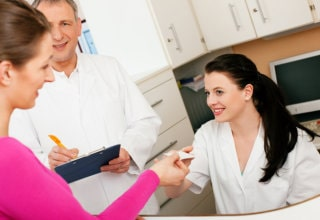 pharmacist accepting woman's insurance