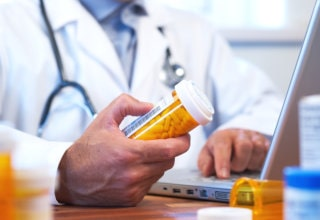 pharmacist holding a bottle of medicine while typing in his laptop